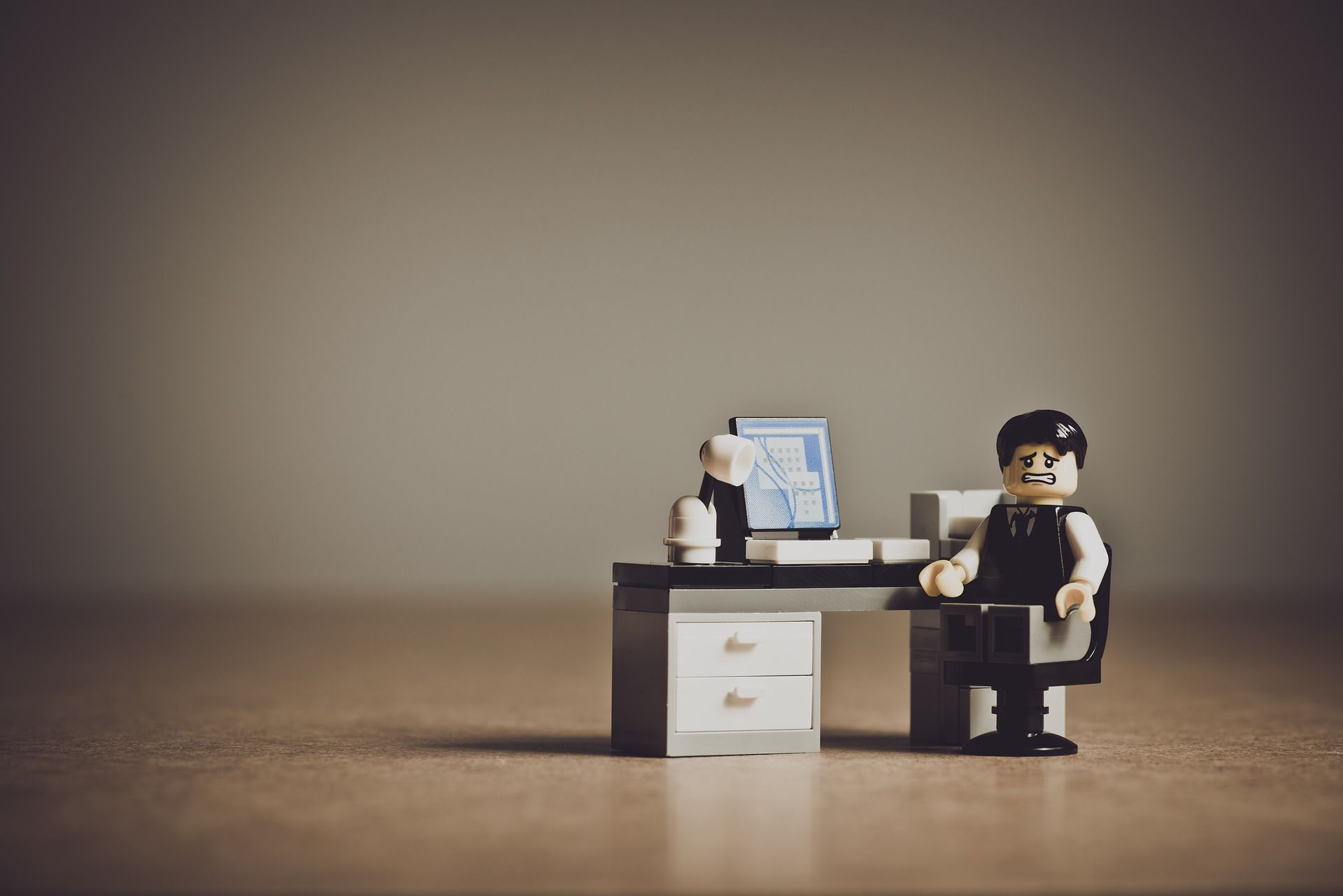 A Lego™ piece man with a stressed expression sitting at a desk.