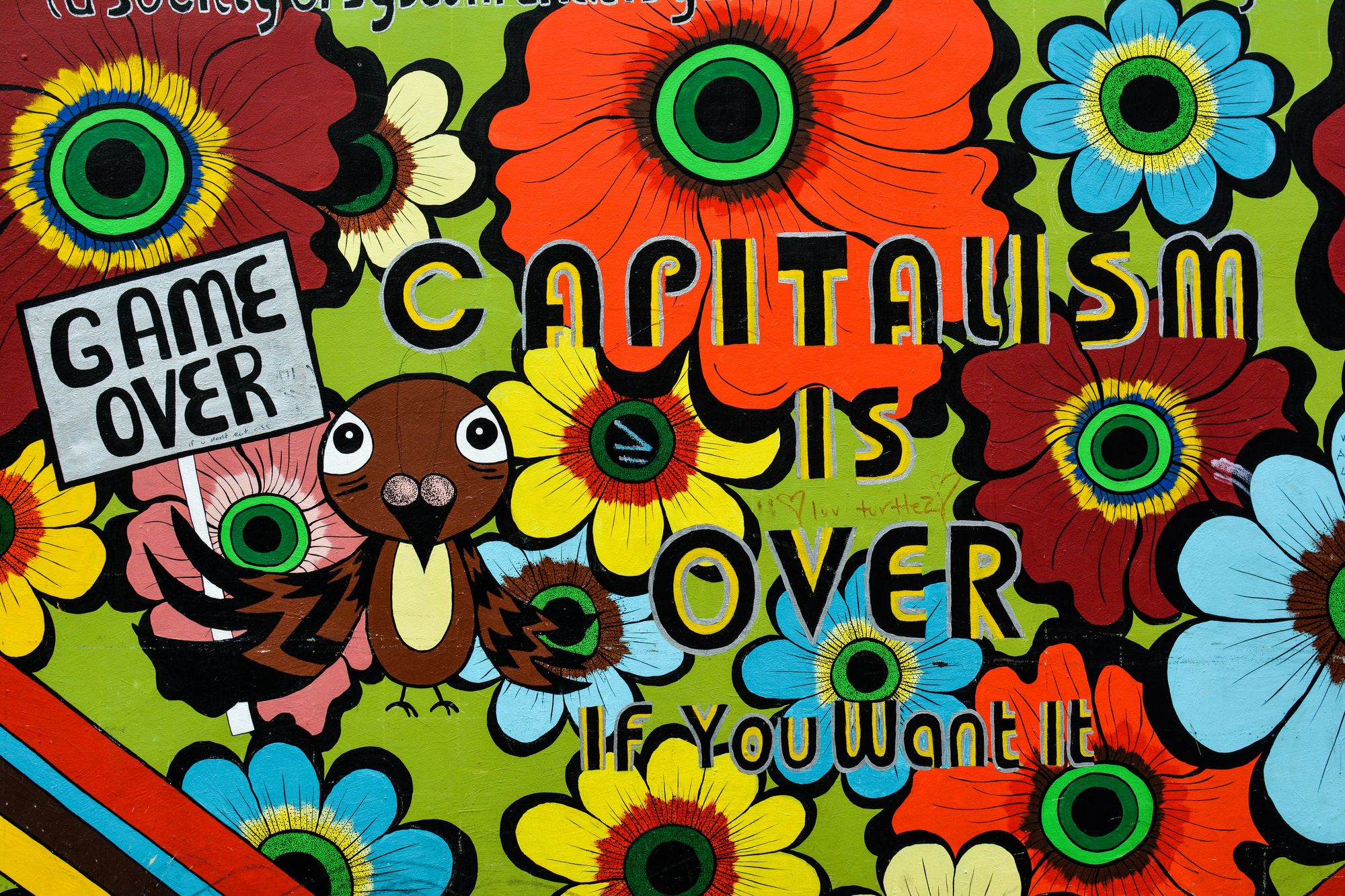 "An illustration of flowers and a bird holding a sign reading ""game over,"" with the words ""Capitalism is over if you want it."""