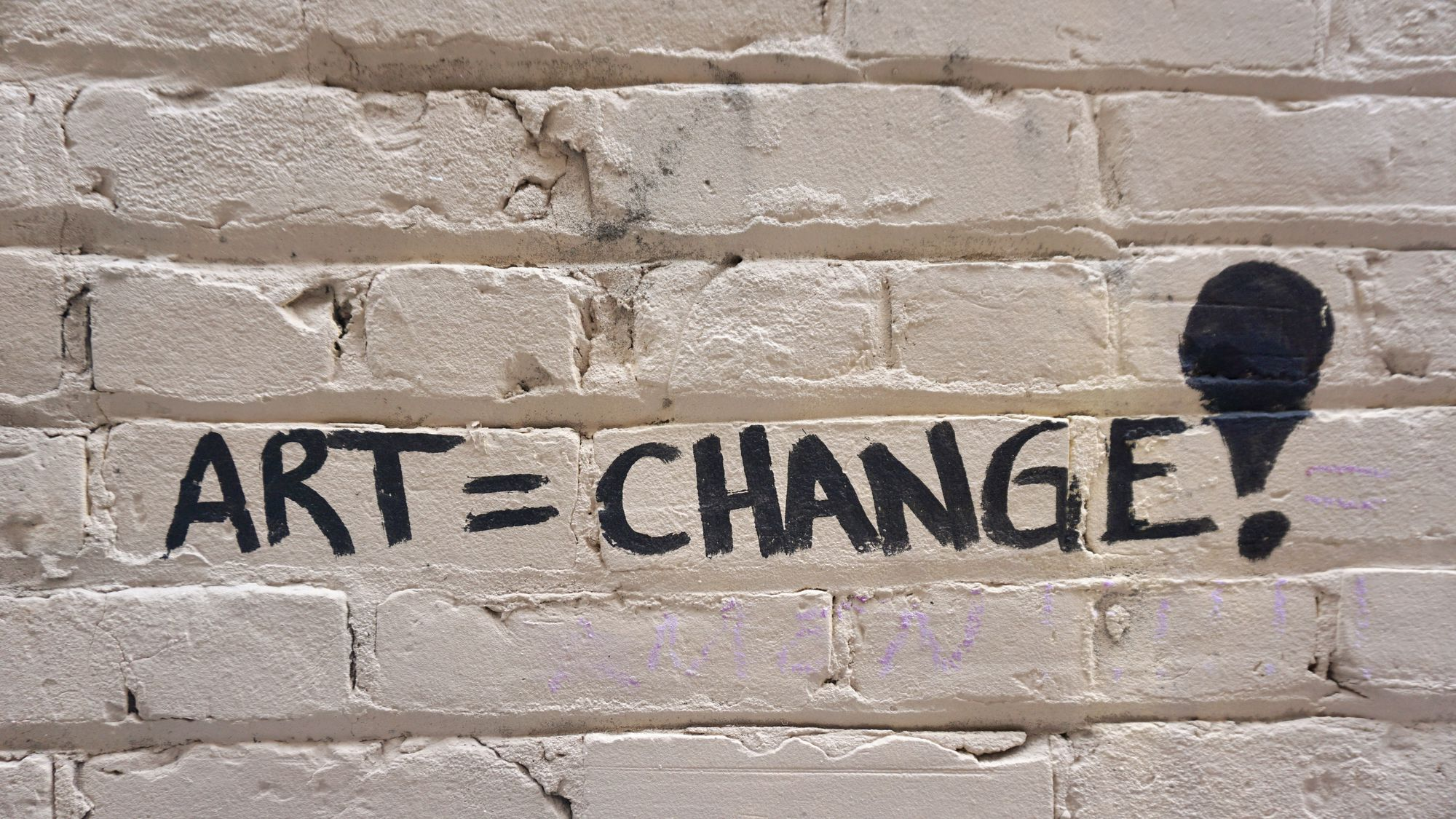 "The words ""art [equals] change!"" written on a brick wall."