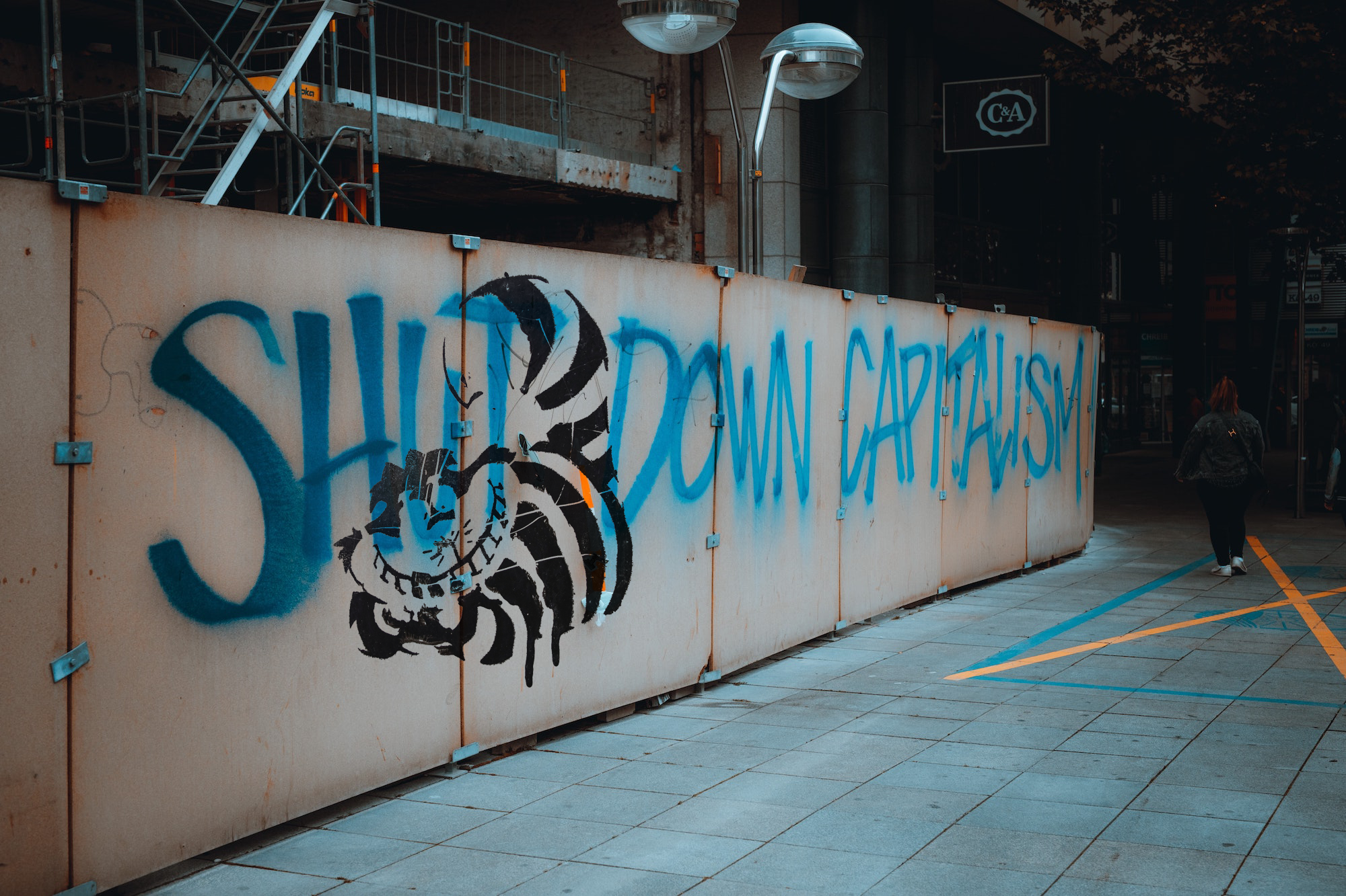 "Graffiti of the Cheshire cat from Alice in Wonderland superimposed (in Photoshop) over an image of graffiti reading ""Shut Down Capitalism"" on a wall, with a figure walking by"